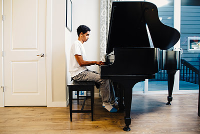 Mixed race boy playing piano - p555m1305920 by Inti St Clair photography