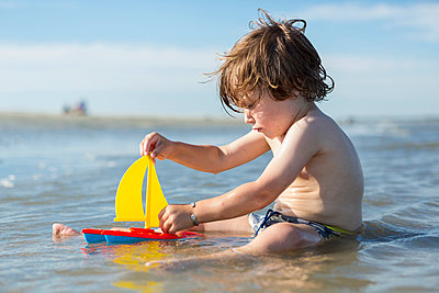 Caucasian boy sitting in ocean playing with toy sailboat - p555m1522749 by Marc Romanelli