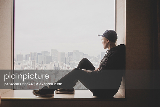 Frau sitzt auf der Fensterbank - p1345m2055574 von Alexandra Kern