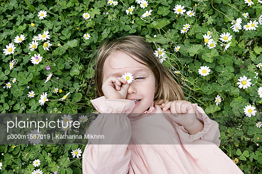 Portrait of little girl lying on flower meadow - p300m1587019 von Katharina Mikhrin