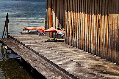 Couple sunbathing near a swimming lake in Austria  - p1540m2175069 by Marie Tercafs
