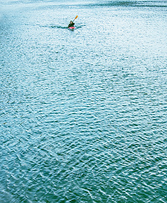Male kayaker kayaking on river, distant view, Domodossola, Piemonte, Italy - p429m2091472 by Guido Cavallini