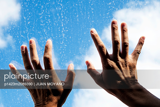 Hands against a dirt glass, with the sky in the background - p1423m2089390 von JUAN MOYANO