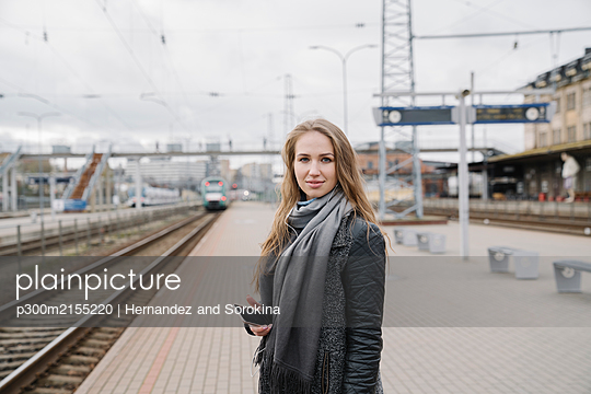 Portrait of smiling young woman with smartphone standing on platform - p300m2155220 by Hernandez and Sorokina