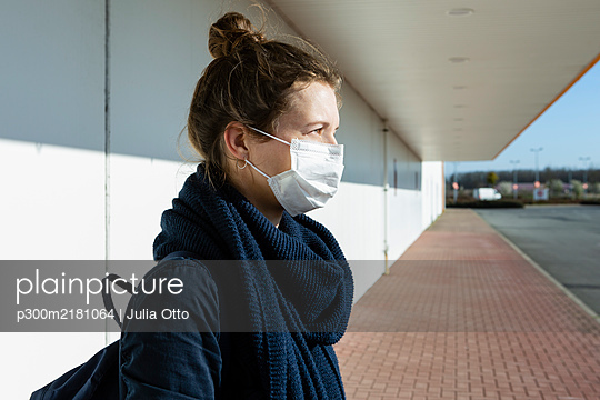 Portrait of woman wearing mask at an empty street - p300m2181064 by Julia Otto
