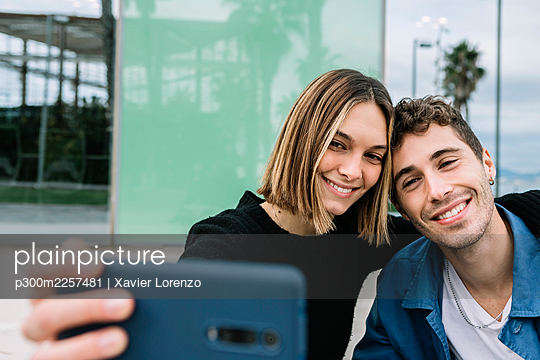Smiling couple taking selfie outdoors - p300m2257481 by Xavier Lorenzo