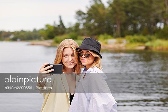 Two friends taking selfie at lakeside - p312m2299656 by Plattform
