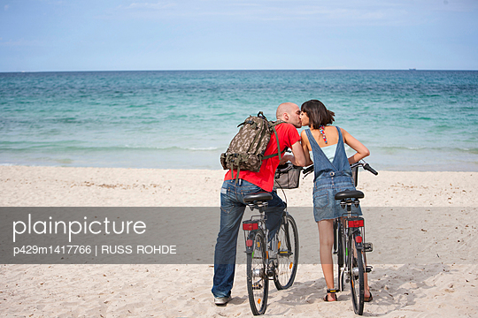 Couple on bicycles on the beach, Mallorca, Spain - p429m1417766 by RUSS ROHDE