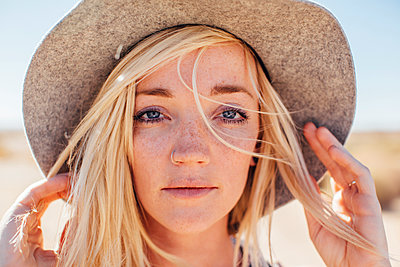 Close-up portrait of woman in sun hat enjoying vacation at desert on sunny day - p1166m1227800 by Cavan Images