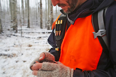 Male hunter checks his GPS while hunting in Colorado. - p1166m2162467 by Cavan Images