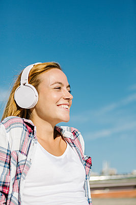 Happy woman listening music through headphone looking away against blue sky on sunny day - p300m2226695 by Xavier Lorenzo