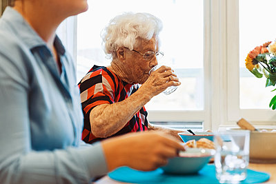 Senior woman drinking water while sitting with daughter at dining table - p426m1468264 by Maskot