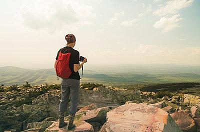Caucasian hiker standing on rocky hilltop - p555m1411150 by Aleksander Rubtsov