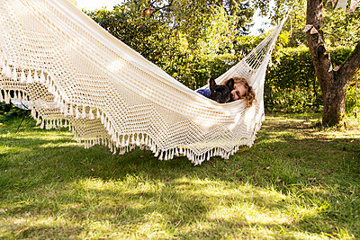 Man with dog relaxing in hammock - p788m2031186 by Lisa Krechting