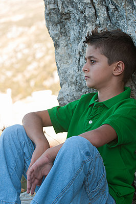 Serious boy sat outdoors looking away  - p794m1119729 by Mohamad Itani