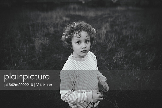 Girl with curly head in the garden - p1642m2222210 by V-fokuse