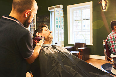 Man receiving a shave in barbershop - p1023m2135777 by Trevor Adeline