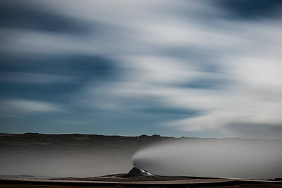 Scenic view of volcano erupting steam against cloudy sky - p1166m1531307 by Cavan Images