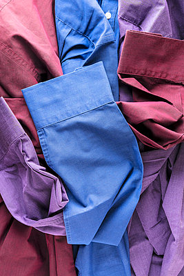 Three shirts, dark red, blue and purple, lying together and showing their sleeve cuffs - p1302m2122527 by Richard Nixon