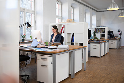 Woman working at desk in office - p300m1459813 by Florian Küttler