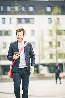 Smiling businessman walking in the city with cell phone and earphones - p300m2103928 by Uwe Umstätter
