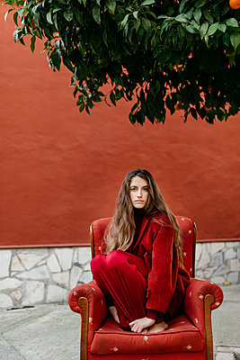 Portrait of young woman with long brown hair dresses in red crouching on red lounge chair - p300m2160710 von Tania Cervián