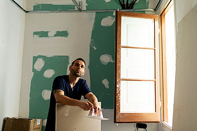 Thoughtful construction worker working in a house - p300m2207037 by Valentina Barreto