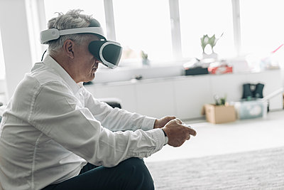 Businessman wearing virtual reality eyeglasses playing video game while sitting at office - p300m2226119 by Gustafsson