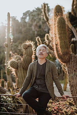 Mature man with eyes closed sitting on railing with cactus plants in background - p300m2274762 by Gala Martínez López