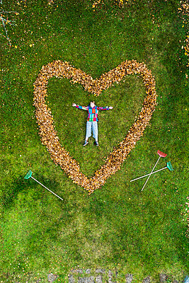 Woman lying in heart made out of fallen leaves - p312m2118568 by Johner