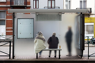 People waiting for the bus behind a frosted glass - p589m1152639 by Thierry Beauvir