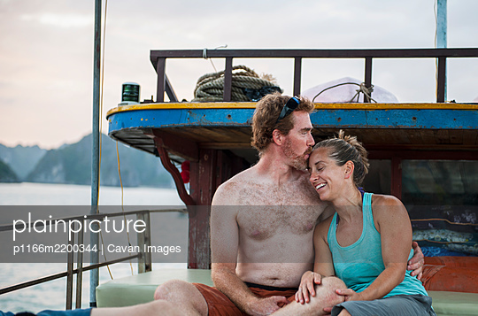 mid adult couple relaxing on a boat in Halong Bay in Vietnam - p1166m2200344 by Cavan Images