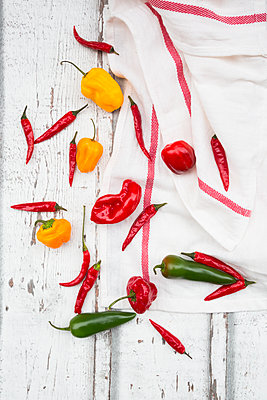 Various chili pods on kitchen towel and wood - p300m1505507 by Larissa Veronesi