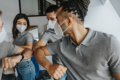 Male and female physical therapists wearing protective face masks doing elbow bump - p300m2276837 by Mareen Fischinger