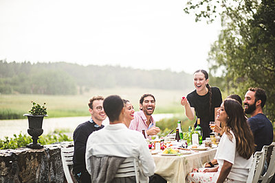 Cheerful male and female friends enjoying dinner party in backyard during weekend - p426m2036160 by Maskot