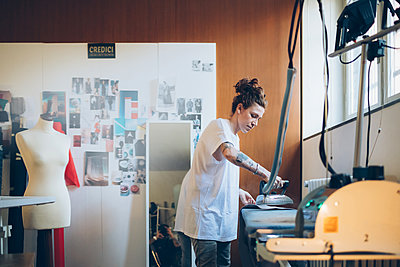 Fashion designer ironing in her work studio - p429m2058372 by Eugenio Marongiu