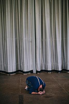 Mann kniet auf der Bühne und verbirgt sein Gesicht - p586m963020 von Kniel Synnatzschke