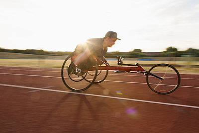 Determined teenage boy paraplegic athlete speeding along sports track in wheelchair race - p1023m2067526 by Martin Barraud