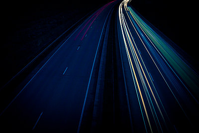 Streaks of coloured light making long lines left by vehicles driving along a road in the night. - p1057m1510622 by Stephen Shepherd
