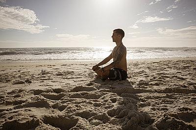 Mann meditiert auf dem Strand im Sonnenschein - p1640m2261023 von Holly & John