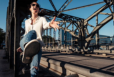 Young woman with sunglasses kicking in the air on a bridge in the evening light - p300m2144879 by Wilfried Feder