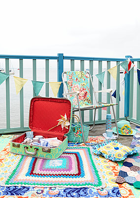 Folding chair and vintage suitcase on painted decking with bunting and blanket - p349m919996 by Fiona Kennedy
