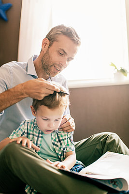 Boy reading book while father combing his hair at home - p426m1179353 by Kentaroo Tryman