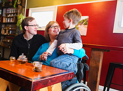 Paraplegic mother holding son in tea shop - p555m1410667 by PhotoAbility