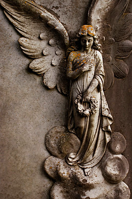 Figure of winged angel holding wreath on stone memorial - p5970165 by Tim Robinson