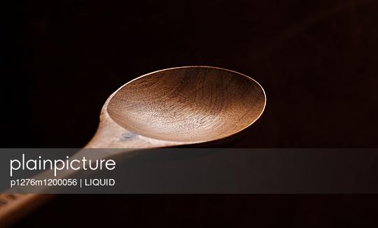 Hölzerner Kochlöffel vor schwarzem Hintergrund  - p1276m1200056 von LIQUID
