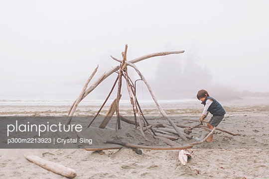 Boy arranging wood logs for campfire at beach during foggy weather - p300m2213923 by Crystal Sing