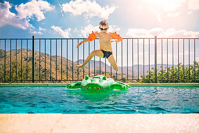 Boy jumping on inflatable crocodile in swimming pool - p1072m2195684 by Neville Mountford-Hoare