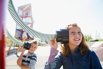 Boy and girl listening to tubes sunny playground - p1192m1078345f by Hero Images