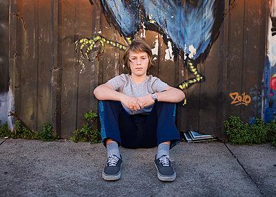 Boy Sitting along Fence - p1503m2020417 by Deb Schwedhelm